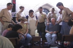 A Missions Prayer Meeting lay their hands on Buck and the rest of the team